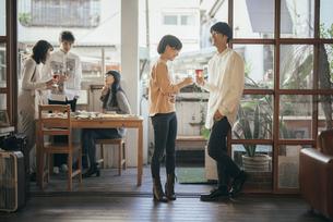 ホームパティーで乾杯する男女。背景に複数人の写真素材 [FYI01248121]