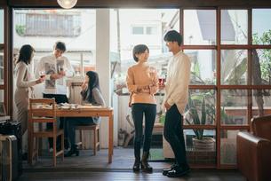 ホームパティーでワイングラスを持ちながら談笑する男女。(全体)の写真素材 [FYI01248122]