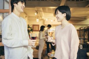 ホームパーティー。ワイングラスを持つ男女。談笑しているの写真素材 [FYI01248124]