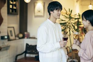 ホームパーティー。ワイングラスを持つ男女。微笑んでいる男性にピント合わせの写真素材 [FYI01248126]