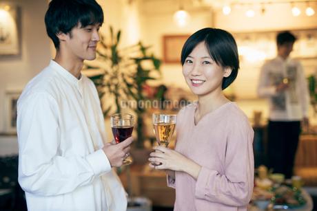 ホームパーティー。ワイングラスを持つ男女。正面を向いて微笑む女性。の写真素材 [FYI01248128]