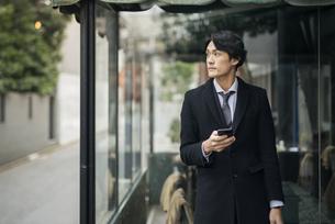 建物の前で電話を手に持っているビジネス男性。コートを着ている。の写真素材 [FYI01248200]