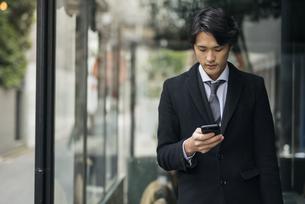 建物の前で電話をながめるビジネス男性。コートを着ている。の写真素材 [FYI01248204]