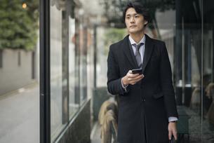 建物の前で電話を手に持っているビジネス男性。コートを着ている。の写真素材 [FYI01248207]