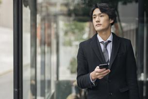 建物の前で電話を手に持っているビジネス男性。コートを着ている。(アップ)の写真素材 [FYI01248209]