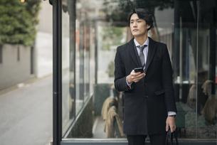 建物の前で電話を手に持っているビジネス男性。コートを着ている。の写真素材 [FYI01248213]