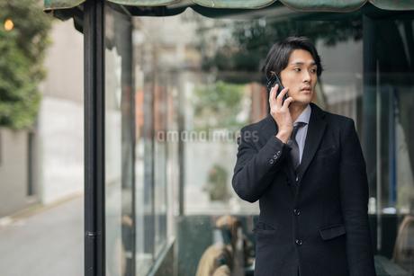 建物の前で電話しているビジネス男性。コートを着ている。の写真素材 [FYI01248215]
