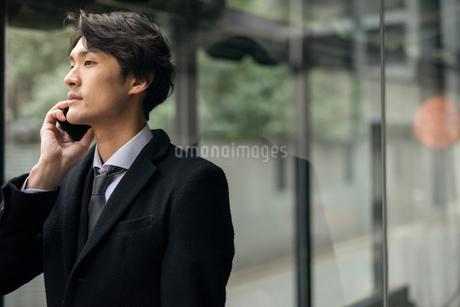 建物の前で電話しているビジネス男性。コートを着ている。の写真素材 [FYI01248218]