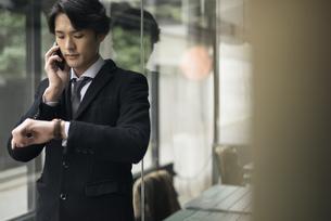 建物の前で時計を見ながら電話しているビジネスマンの写真素材 [FYI01248224]