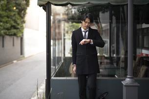 建物の前で時計を見ながら立っているビジネスマンの写真素材 [FYI01248225]