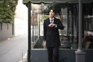 建物の前で時計を見ながら立っているビジネスマンの写真素材 [FYI01248227]