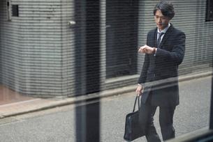 ビジネスマン。時計を眺めながら歩いている。の写真素材 [FYI01248232]