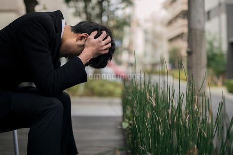 考えるサラリーマン男性。悩んでいる。頭を抱え込むの写真素材 [FYI01248258]