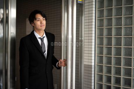 建物から出ようとしているビジネスマンの写真素材 [FYI01248286]