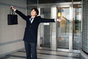 会社の外に出たサラリーマン。笑顔。伸びをしているの写真素材 [FYI01248289]
