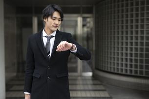 会社の外に出たサラリーマン。時計を見ている。の写真素材 [FYI01248291]