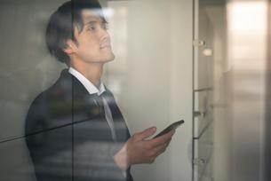 建物の中。スマホをもつビジネスマンの写真素材 [FYI01248526]