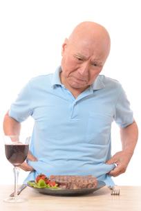 ステーキを前に悩む肥満のシニアの写真素材 [FYI01248957]