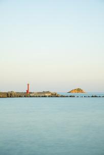赤い灯台と島の見える朝の港の写真素材 [FYI01250895]