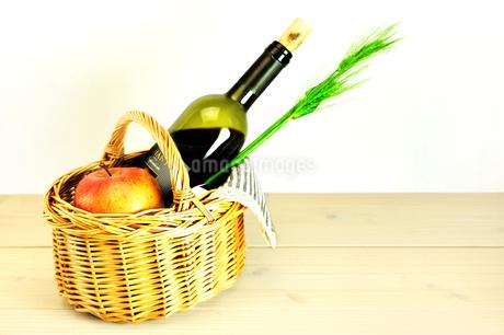 バスケットに入ったワインとリンゴと麦の写真素材 [FYI01251749]