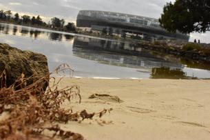 浜辺の足跡と川の向こうのスタジアムの写真素材 [FYI01252740]