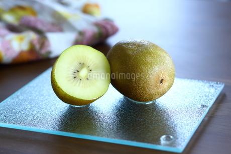 ガラスプレートにのったキウイとテーブルの写真素材 [FYI01254136]