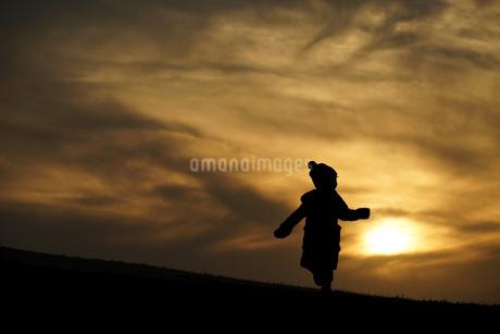 夕暮れの丘に立つ少女2の写真素材 [FYI01254669]