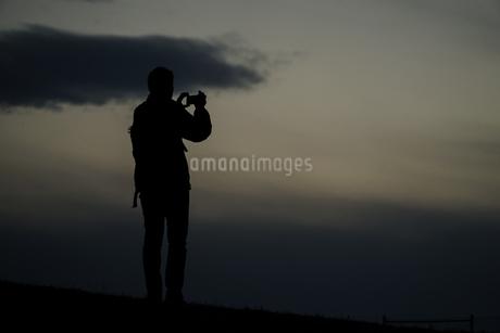 丘に立つ男性のシルエットの写真素材 [FYI01254901]