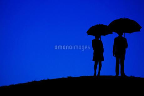 夜の丘に立つ傘をさす男女の写真素材 [FYI01255245]