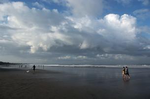 遠浅の浜辺を歩く人の写真素材 [FYI01255484]