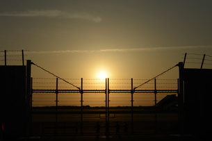 空港の夕日とフェンスの写真素材 [FYI01255514]
