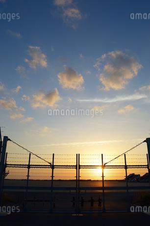 空港の夕日とフェンスの写真素材 [FYI01255517]