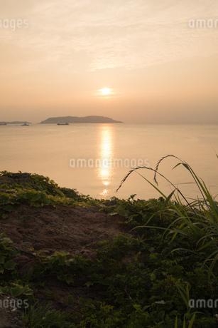 崖から夕日をのぞむシーンの写真素材 [FYI01255551]