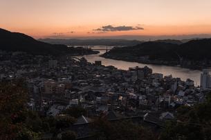 山の上から朝焼けの街を眺めるシーンの写真素材 [FYI01256497]