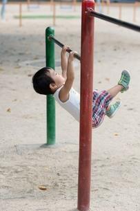 鉄棒をする男の子の写真素材 [FYI01256772]