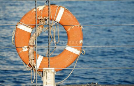 港の柵に掛けてある救命浮き輪の写真素材 [FYI01257502]
