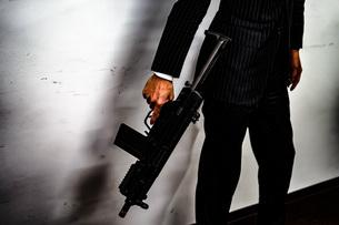 マシンガンを持つ戦うビジネスマンの写真素材 [FYI01257768]