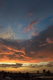 夕焼けに燃えるような雲と都会のシルエットの写真素材 [FYI01259146]