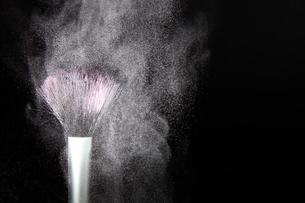 化粧筆と飛散るカラーパウダーの写真素材 [FYI01259291]