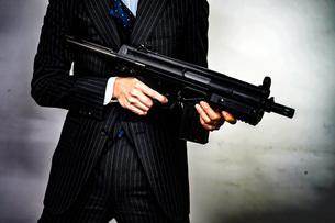 マシンガンを持つ戦うビジネスマンの写真素材 [FYI01259793]