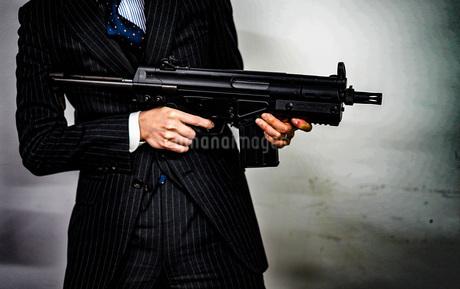 マシンガンを持つ戦うビジネスマンの写真素材 [FYI01259795]