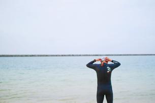 ウェットスーツを着て海の前に立つ男性の写真素材 [FYI01259861]