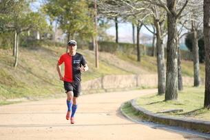 公園でジョギングをする男性の写真素材 [FYI01259868]