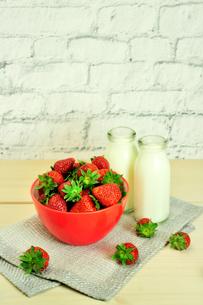 木製テーブルの上の摘みたてイチゴとミルクの写真素材 [FYI01260285]