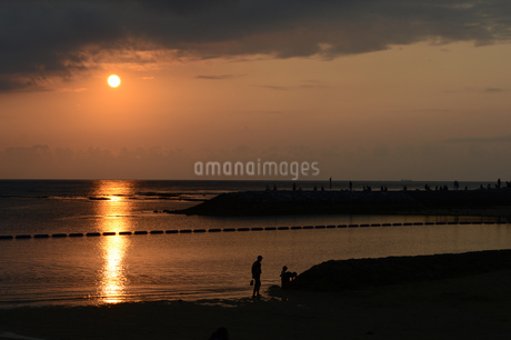 夕日の落ちるビーチにシルエットの人々の写真素材 [FYI01260341]