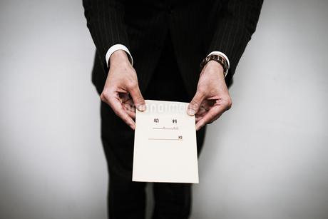 給料袋を渡すビジネスマンの写真素材 [FYI01261229]