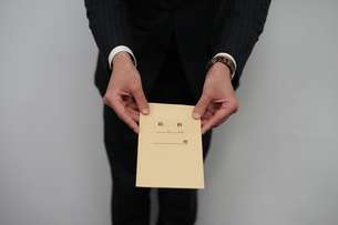 給料袋を渡すビジネスマンの写真素材 [FYI01261230]