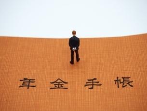 年金手帳とミニチュアの男の写真素材 [FYI01262019]