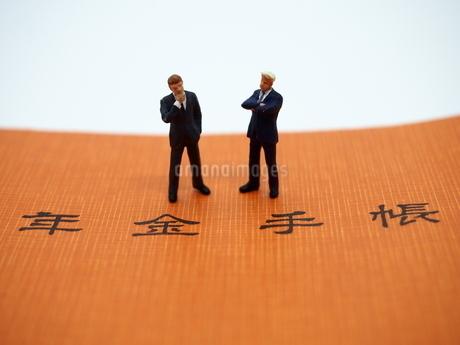 二人のビジネスマンと年金手帳の写真素材 [FYI01262021]