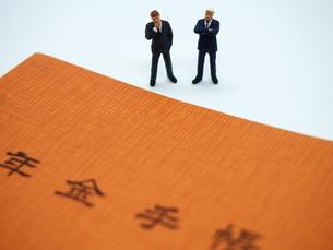 年金手帳とミニチュアのビジネスマンの写真素材 [FYI01262023]